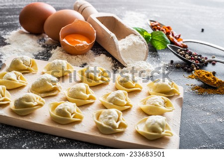 raw ravioli and different products on the black kitchen table - stock photo