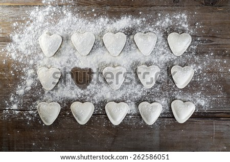 Raw ravioli in the shape of hearts, sprinkle with flour, on dark wooden background. Cooking dumplings. Top view. - stock photo