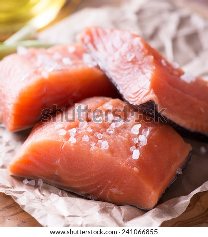 Raw red fish fillet with sea salt over wooden board, selective focus - stock photo