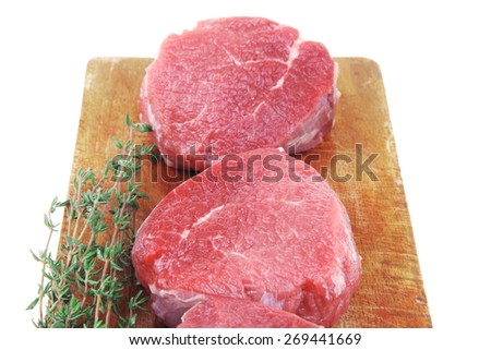 raw red meat : three fresh beef fillet chops with thyme twig on wooden plate . isolated over white background - stock photo