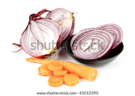 Raw red onion cut in half with slices in a dish and carrot on a reflective white background