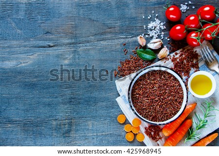 Raw red rice and fresh vegetables ingredients for tasty cooking on rustic wooden background, top view.  Healthy eating or vegetarian concept. - stock photo