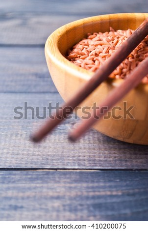 Raw red rice in bowl and wooden chopsticks on rustic shabby background. Selective focus - stock photo
