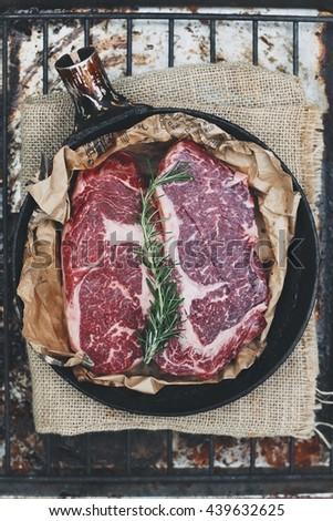 Raw rib eye steak on rustic board - stock photo