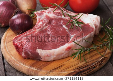 Raw ribeye beef steak on wooden board with rosemary and onion - stock photo