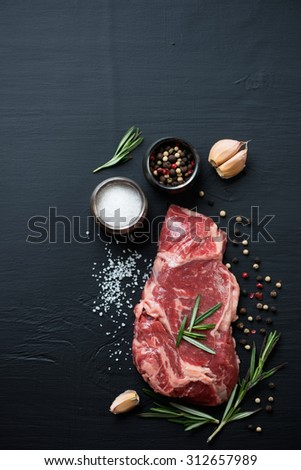 Raw ribeye beefsteak with seasonings, black wooden background, top view - stock photo