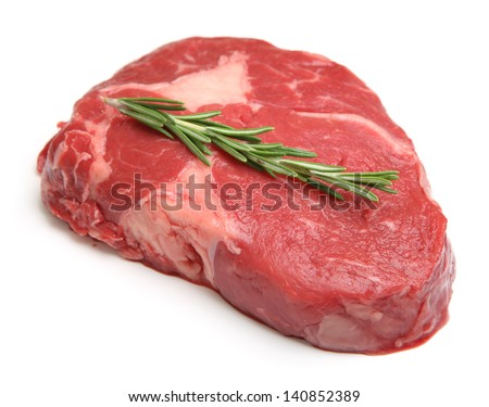 Raw ribeye steak garnished with a sprig of rosemary. - stock photo
