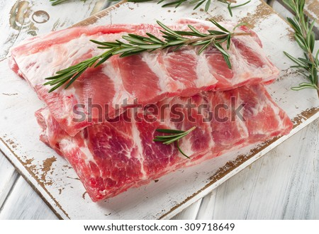 Raw ribs with a rosemary on a white wooden table - stock photo