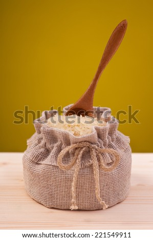 Raw rice in a jute sack with wooden spoon on a wooden surface over dark yellow background