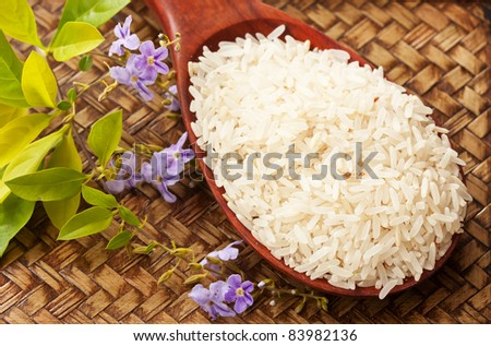 Raw rice in spoon with flower on wood tray - stock photo