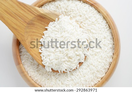 Raw rice in wooden bowl with spoon on white background. - stock photo