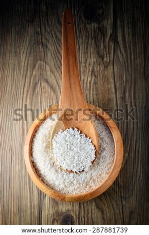 Raw rice in wooden bowl with spoon on wooden background.