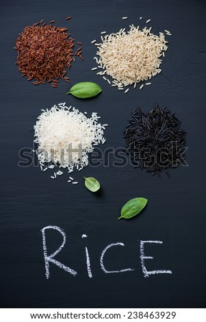 Raw rice kernels of different types on a black wooden surface - stock photo