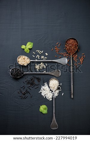 Raw rice of different types in vintage spoons, view from above - stock photo