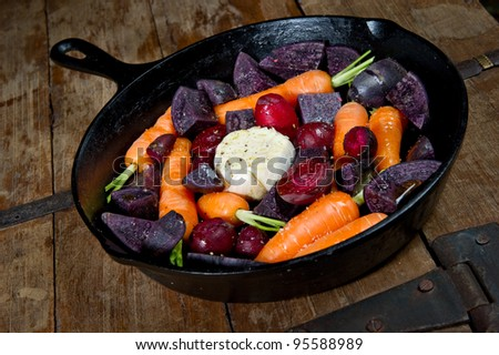 Raw root vegetables in a cast iron skillet ready for the oven. Vegetables include carrots, red beets, garlic and purple potatoes.
