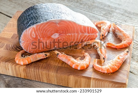 Raw salmon and shrimps on the wooden board - stock photo