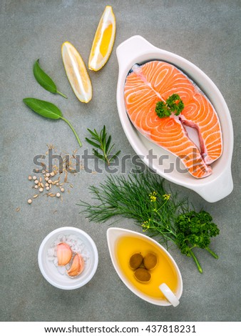 Raw salmon fillet in the white bowl with ingredients olive oil ,sea salt, and herbs  fennel ,sage ,rosemary ,garlic ,pepper and lemon for cooking on concrete background . - stock photo