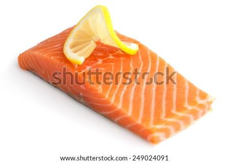 Raw salmon fillet on white. Lemon slice. - stock photo