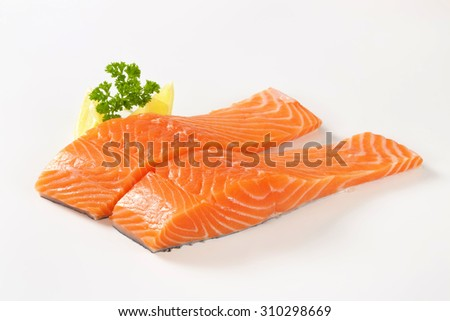 raw salmon fillets with lemon and parsley on white background - stock photo