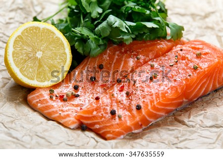 Raw Salmon fish fillet with fresh herbs on crumpled paper - stock photo