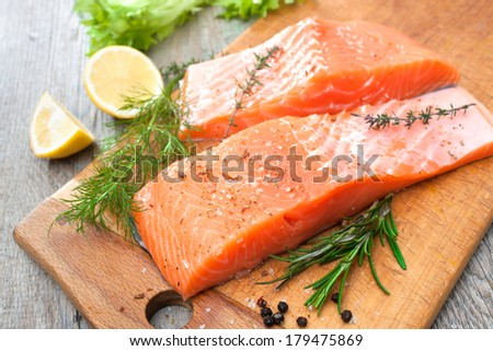 Raw salmon fish fillet with fresh herbs on cutting board - stock photo