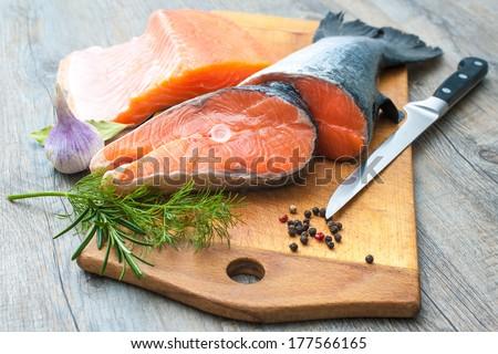Raw salmon fish steaks with fresh herbs on cutting board - stock photo