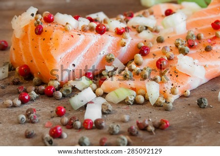 Raw salmon fish with pepper on wooden table - stock photo