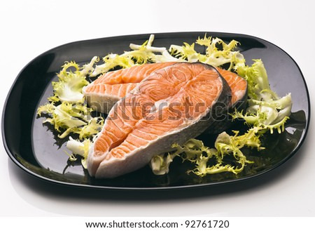 raw salmon slices on a black dish with green salad
