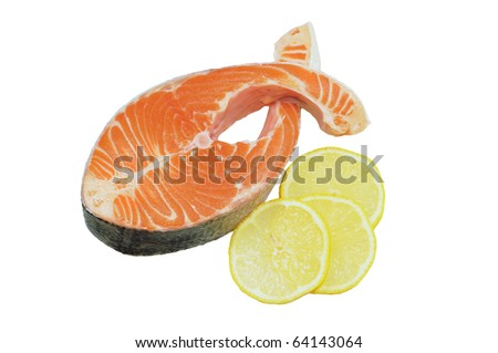 Raw salmon steak in the form of fish, garnished with lemon and herbs. Isolated on white.