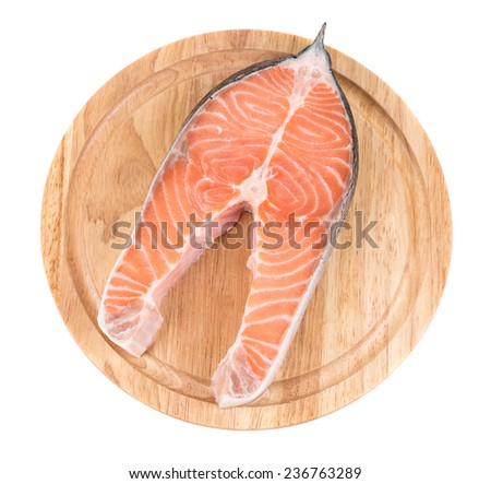 Raw salmon steak on cutting board. Isolated on a white background.