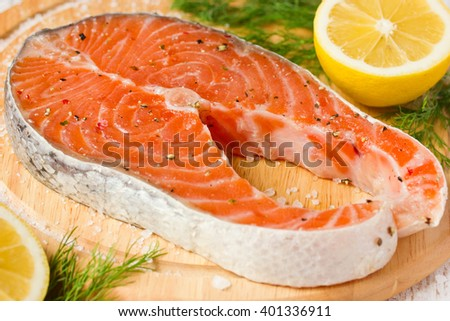 Raw salmon steak on wooden board with salt, pepper, dill and lemon close up - stock photo