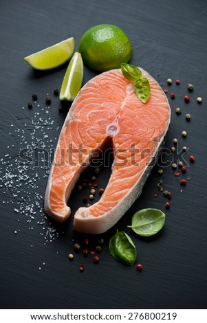 Raw salmon steak with various spices and lime, close-up - stock photo