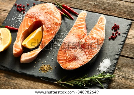 Raw salmon steaks and ingredients on slate background   - stock photo