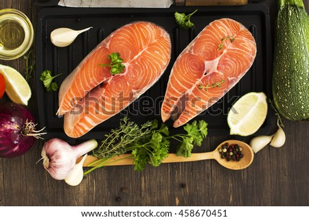 Raw salmon steaks with vegetables ready for grilling - stock photo