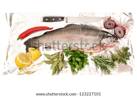 raw salmon trout fish with fresh herbs and spices on foil background - stock photo