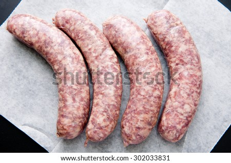 raw sausage links prior to cooking in a cast iron pan - stock photo