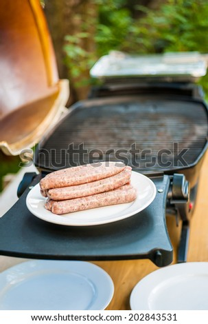 Raw sausages on a plate next to the barbecue - stock photo