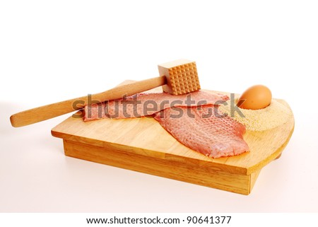 Raw schnitzel with the ingredients, egg and bread crumbs on a cutting board - stock photo