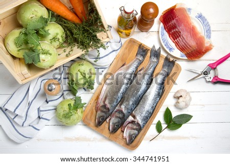 Raw sea bass, kohlrabi, carrots, thyme, garlic, bacon, bay leaf and olive oil on a white table - stock photo