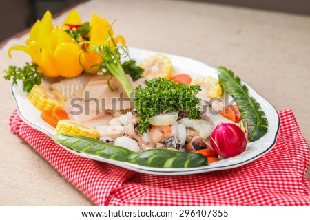 Raw seafood decorated on white plate - stock photo