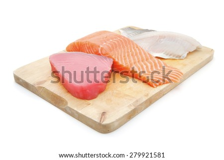 raw set of sea fish food : salmon , red tuna, and sole fish chunks served on wooden plate isolated on white background - stock photo