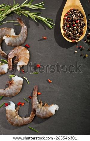 Raw Shrimps on Black Stone Background - stock photo