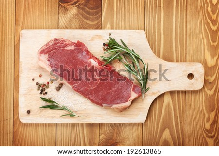 Raw sirloin steak with rosemary and spices on cutting board over wooden table - stock photo