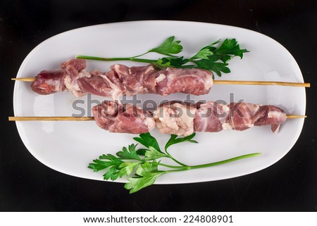 Raw skewer and vegetables on plate - stock photo
