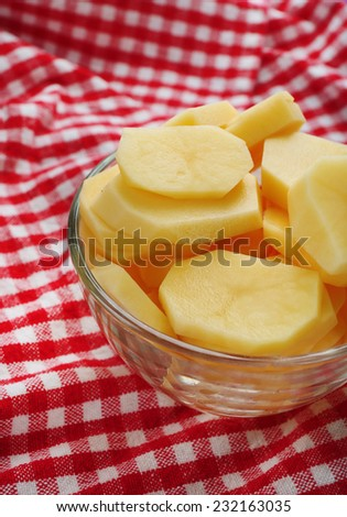 Raw sliced potatoes in glass bowl  on color fabric background