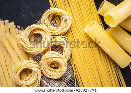 Raw spaghetti on black wooden background, top view place for text - stock photo