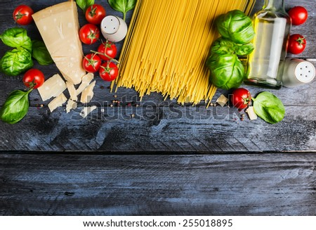Raw spaghetti with tomatoes, basil,parmesan and oil, cooking Ingredients  on blue rustic wooden background, top view, place for text - stock photo