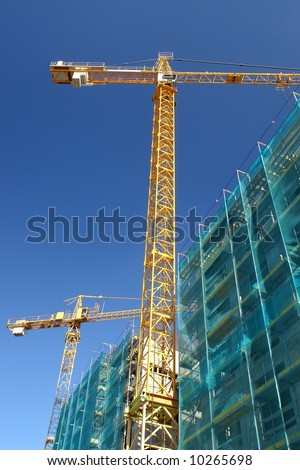 Raw state residential highrise and two yellow jib cranes over clear blue sky - stock photo