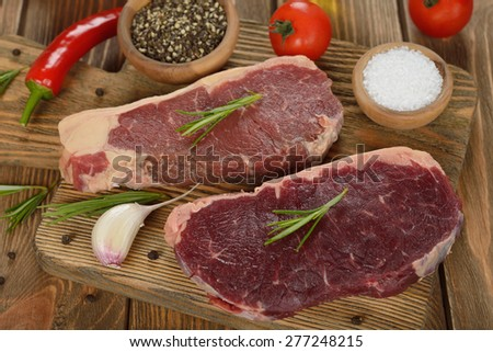 Raw steak on a brown background - stock photo