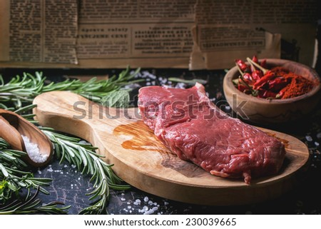 Raw steak on olive cutting board with rosemary herbs and red hot pepper over black wooden table.  - stock photo